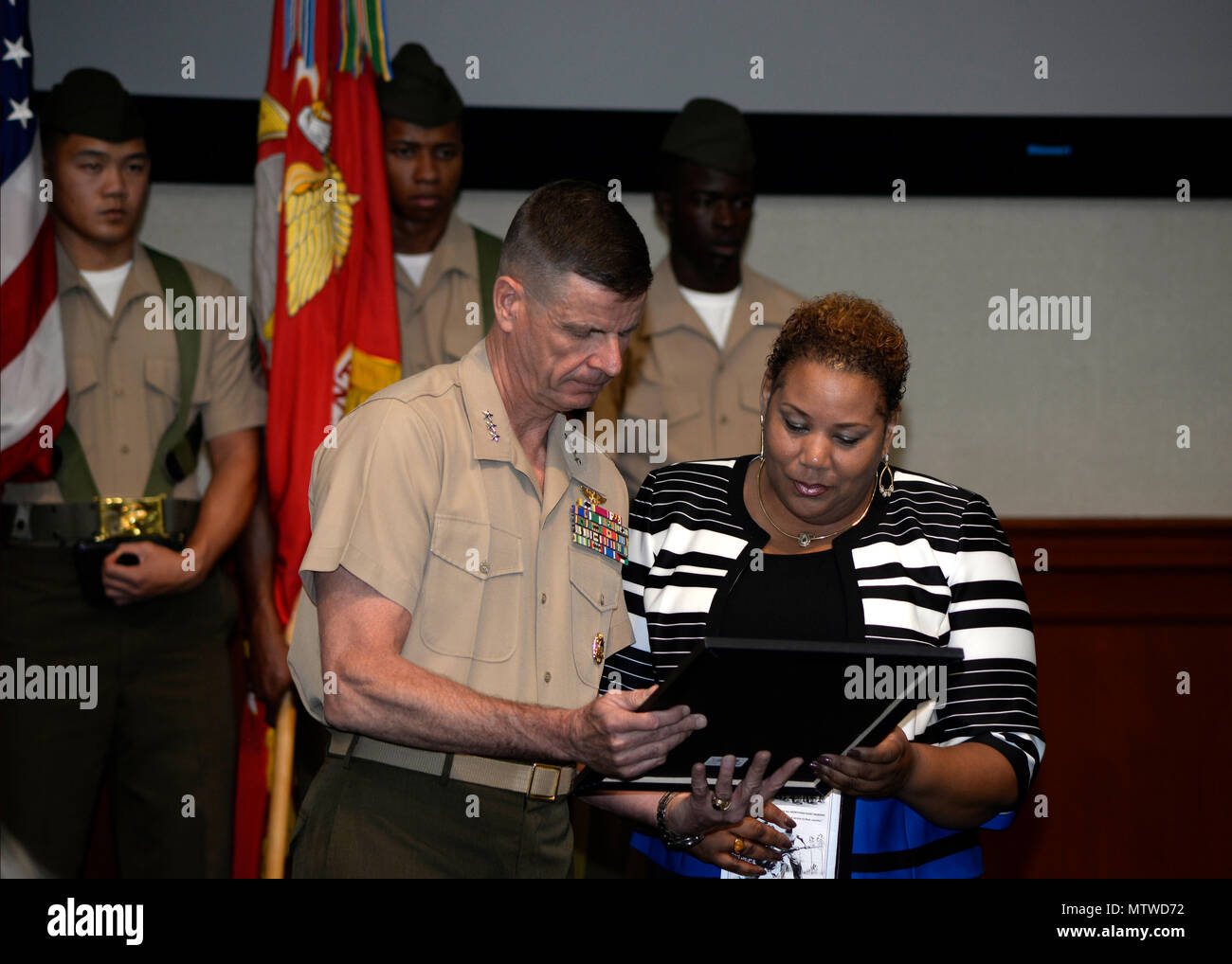 Kim Fountaine, right, accepts a certificate on behalf of her father, U.S. Marine Corps Pfc. Charles Robert Fountain, from Lt. Gen. William D. Beydler, commander of U.S. Marine Forces Central Command, during a Congressional Gold Medal ceremony at MacDill Air Force Base, Fla., Jan. 27, 2017. The certificate was awarded to Fountain who served in the Montford Point Marines, an all African-American unit that was segregated throughout World War II. (U.S. Air Force photo by Tech. Sgt. Krystie Martinez) - Stock Image