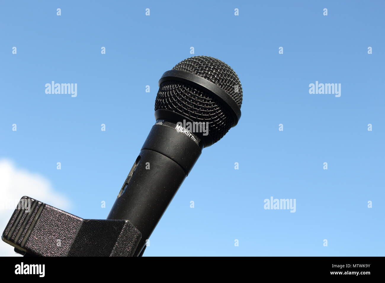 Close-up of black, shiny microphone with clear blue sky background on a sunny summer's day - Stock Image