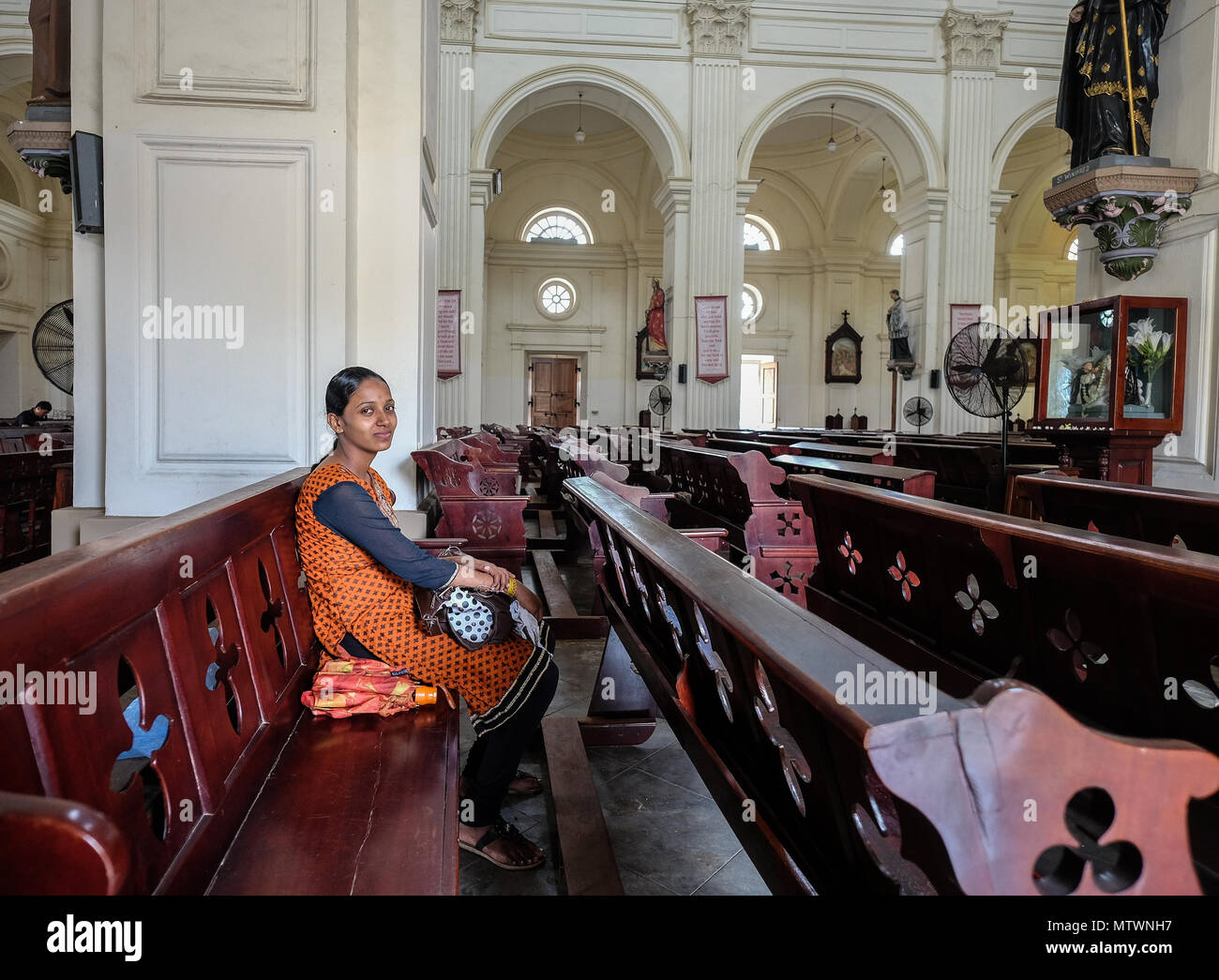 Galle, Sri Lanka - Sep 9, 2015. A young woman praying at the church in Galle, Sri Lanka. Galle was the main port on the island in the 16th century. Stock Photo