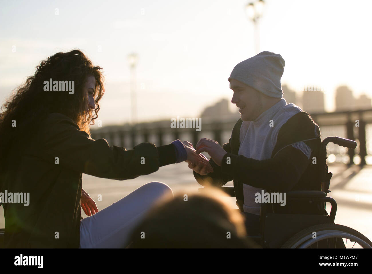 Young disabled man in wheelchair makes a proposal to his girlfriend on the sunlight - Stock Image