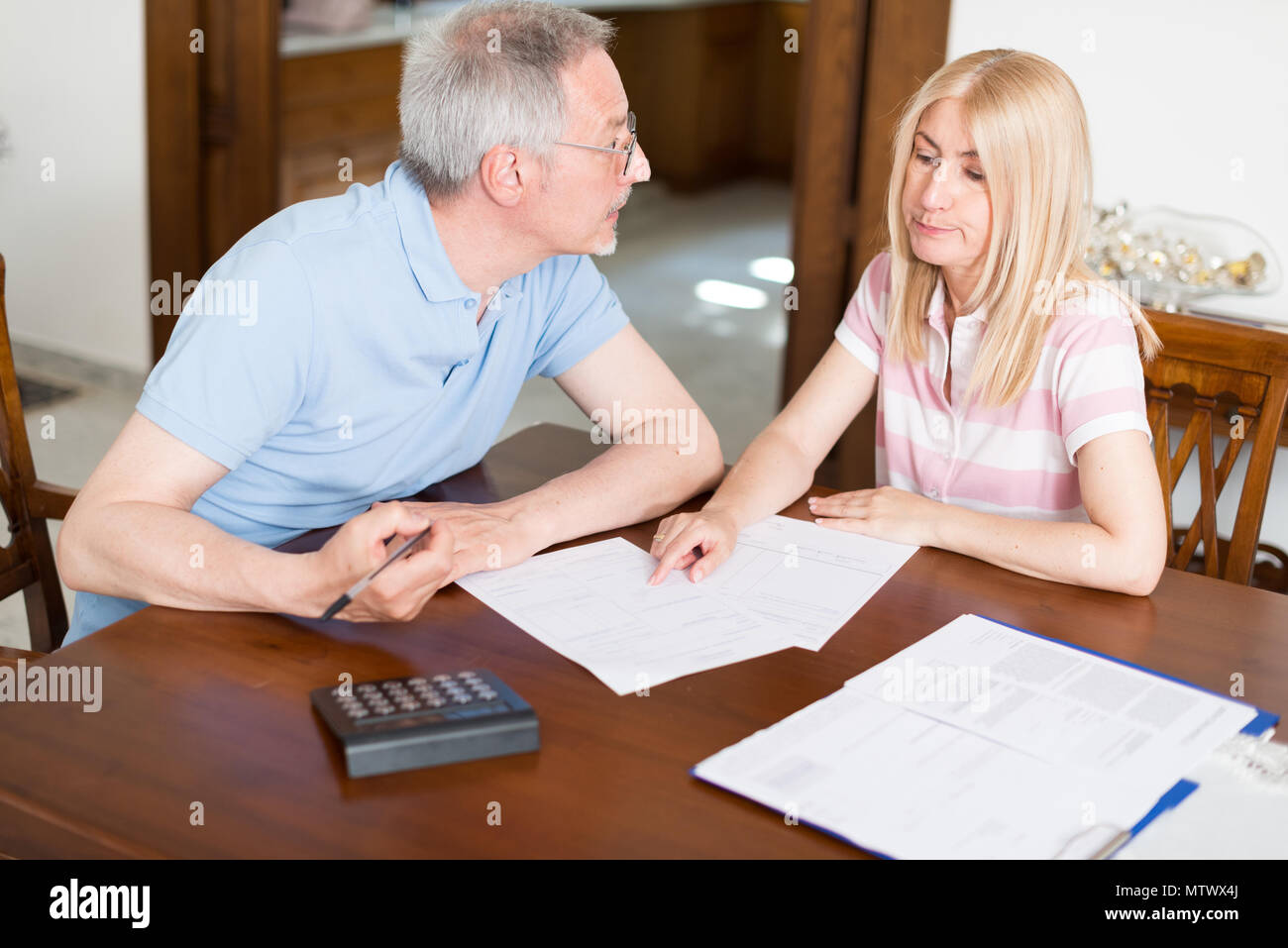 Couple calculating their expenses together - Stock Image