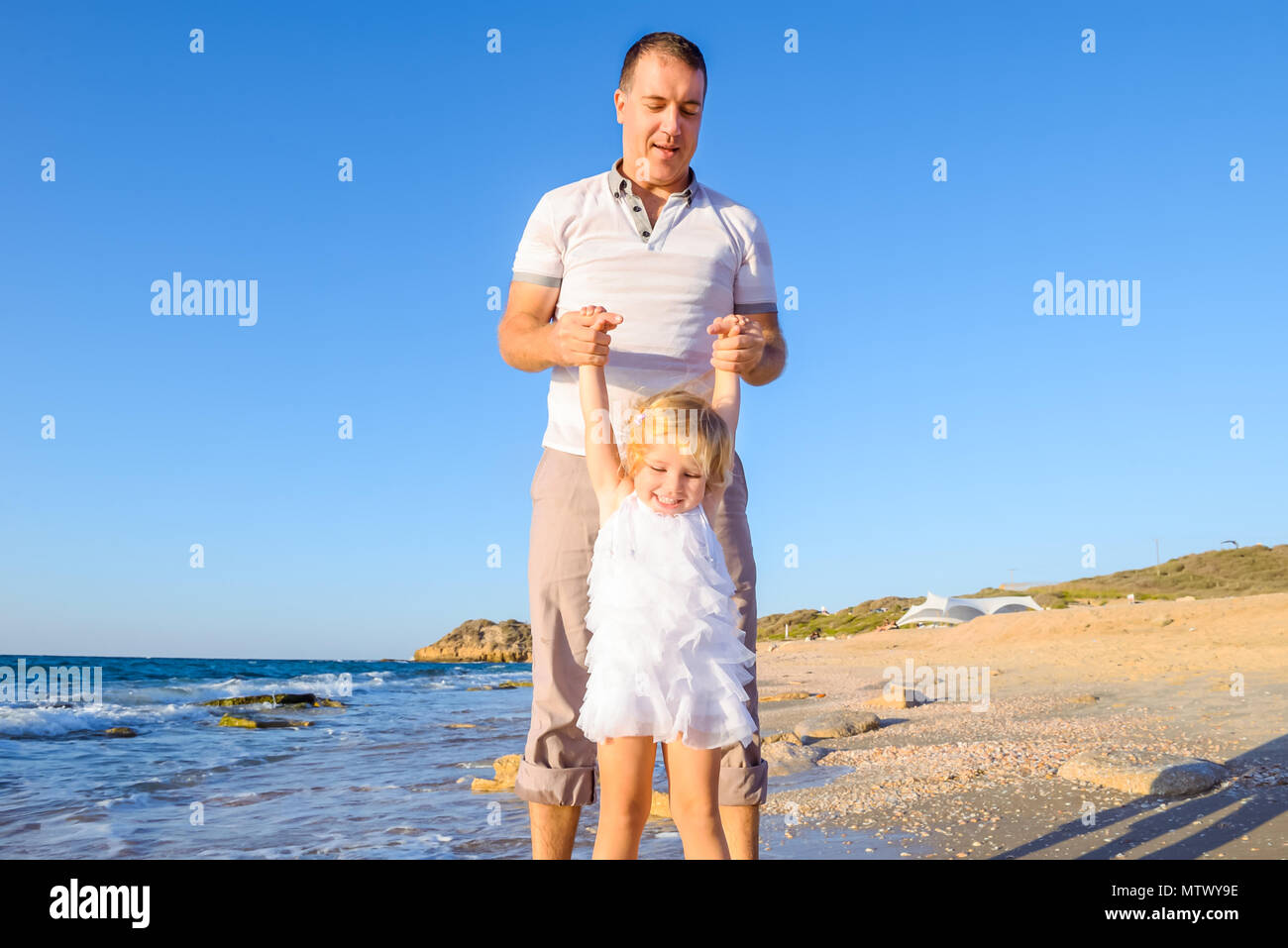 Happy blondy child girl with her father holding hands and having fun walking on the beach. Family vacation, travel concept. Bright sunlight. Copy spac - Stock Image