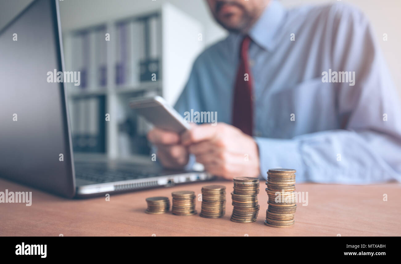 Coin stacker, businessman with stacked money in the office doing accountancy, budgeting and tax calculations Stock Photo