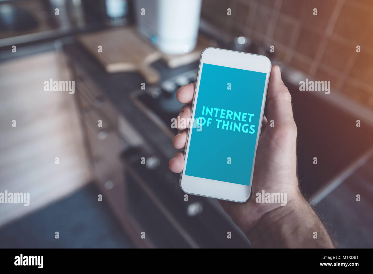 Internet of things, smartphone connecting with ceramic stove top. Smart home kitchen appliance connecting with mobile phone and exchanging data. - Stock Image