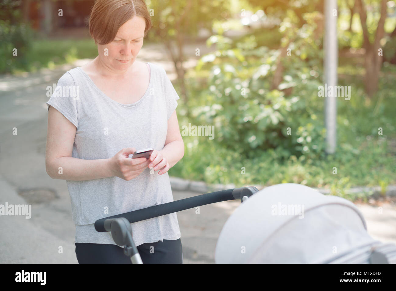 Mother dialing phone number while pushing baby stroller on the street in casual sport clothing - Stock Image