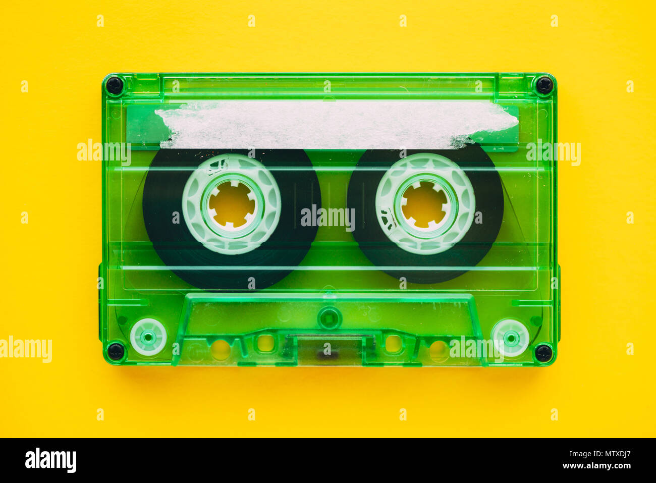 Audio cassette tape on yellow background, retro vintage technology - Stock Image