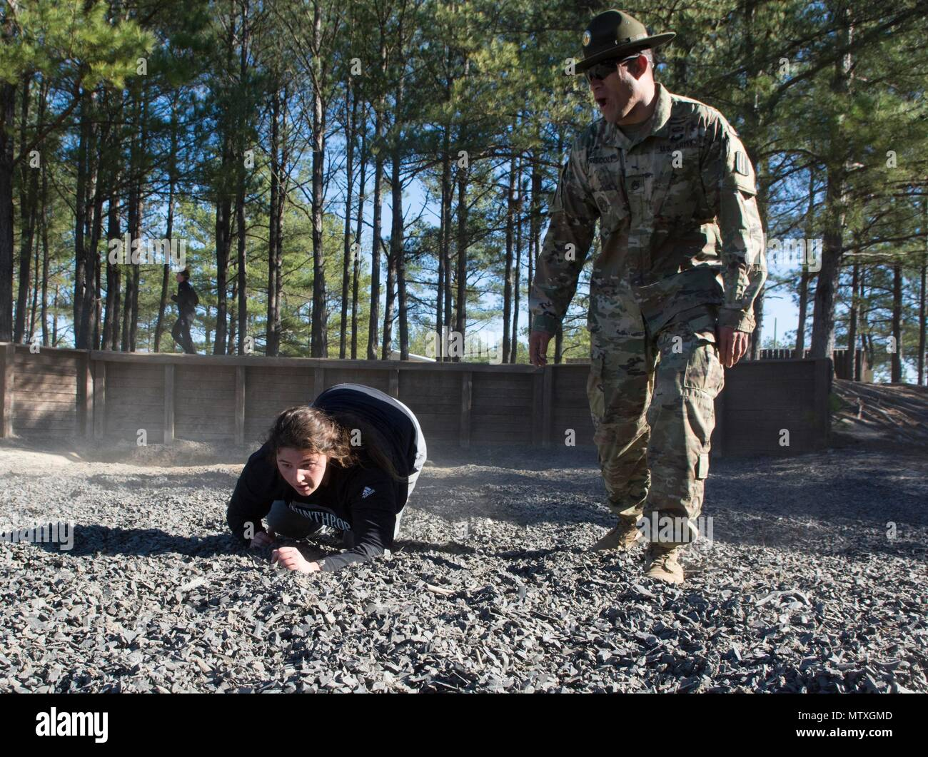 Alaina Girani, a junior goalie, and Wirtz, Va. native, on the Winthrop University Women's Lacrosse Team, is motivated to crawl to the end of Fit to Win 2 by Staff Sgt. Eric M. Driscoll, a drill sergeant with Alpha Company, 1st Battalion, 13th Infantry Regiment, during a team building exercise on Fort Jackson Jan. 28. (U.S. Army photo by Robert Timmons, Fort Jackson Public Affairs/Released) - Stock Image