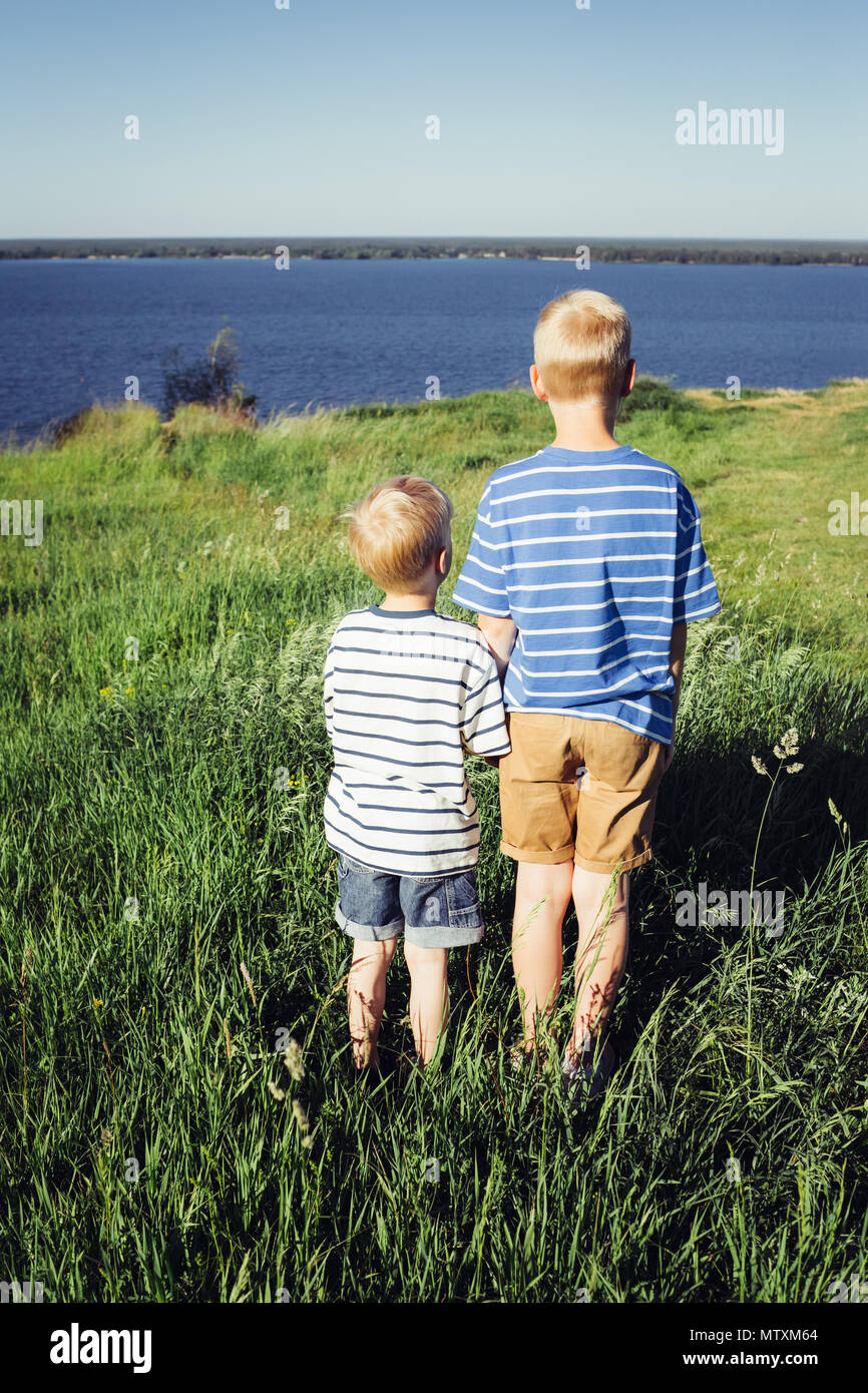 Two blond boys looking into the distance. Conceptual realism. Nature and people. - Stock Image