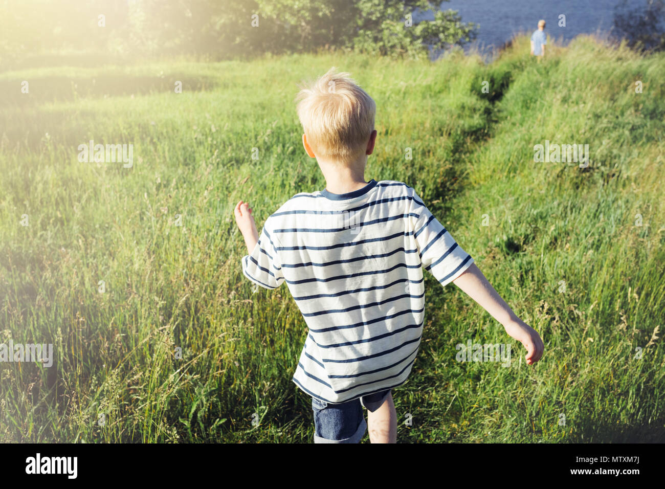 Blond boy running into the distance. A child in nature. Conceptual realism. - Stock Image