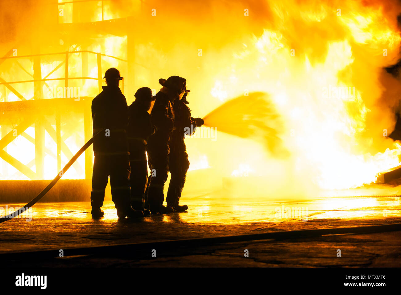 JOHANNESBURG, SOUTH AFRICA - MAY, 2018 Firefighters spraying water at fire during firefighting training exercise Stock Photo