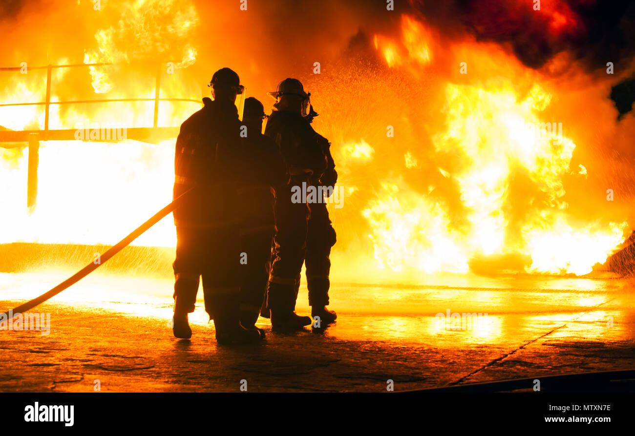 JOHANNESBURG, SOUTH AFRICA - MAY, 2018 Firefighters standing in front of fire with hose during fighting training exercise - Stock Image