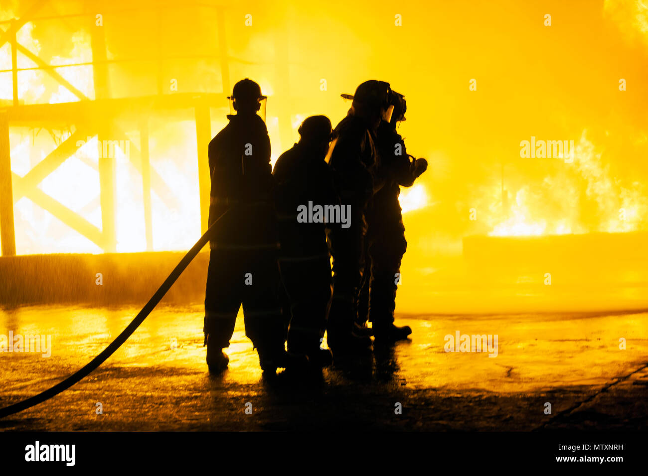 JOHANNESBURG, SOUTH AFRICA - MAY, 2018 Group of firefighters standing in front of fire with hose during fighting training exercise - Stock Image