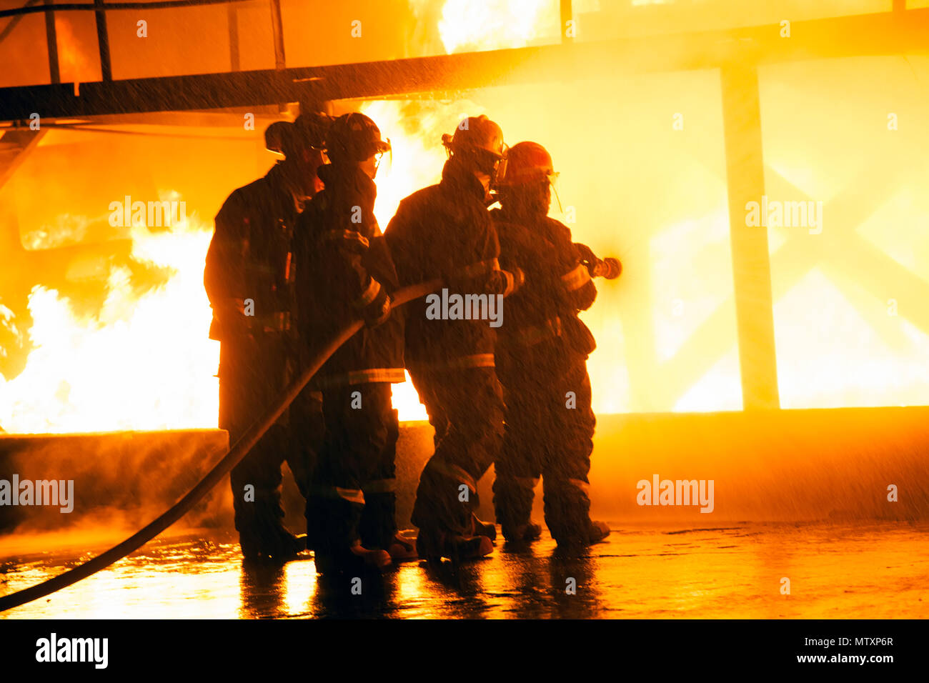 JOHANNESBURG, SOUTH AFRICA - MAY, 2018 Closeup of firefighters fighting fire during firefighting training exercise - Stock Image