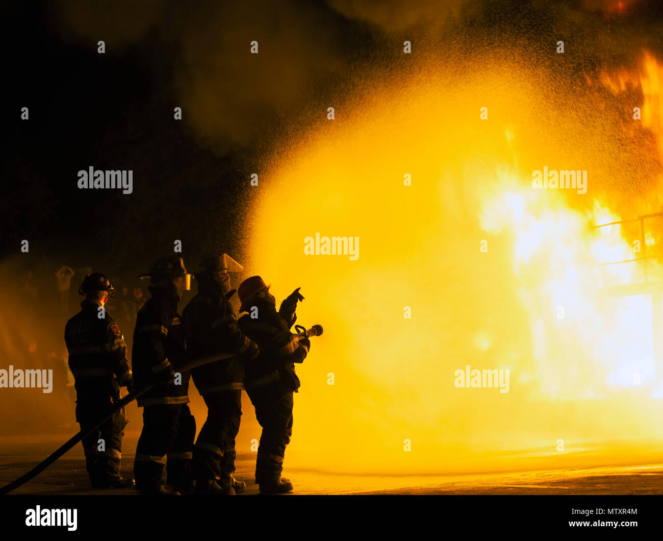 JOHANNESBURG, SOUTH AFRICA - MAY, 2018 Firefighters pointing towards fire during fighting training exercise Stock Photo