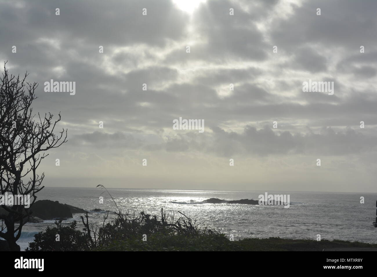 Sunlight gleaming through clouds onto the sea - Stock Image