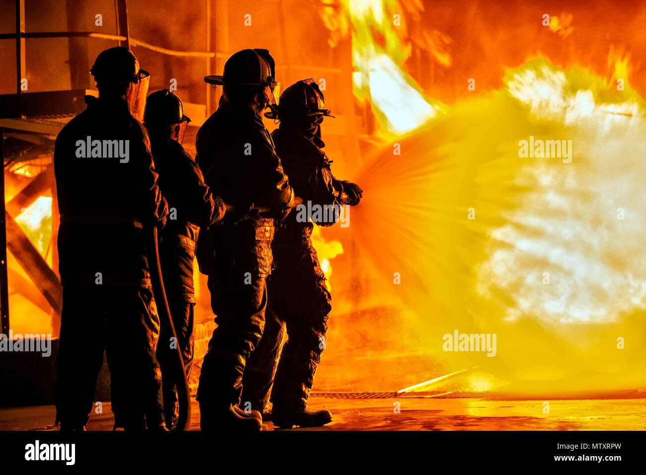 JOHANNESBURG, SOUTH AFRICA - MAY, 2018 Firefighters spraying down fire during firefighting training exercise Stock Photo
