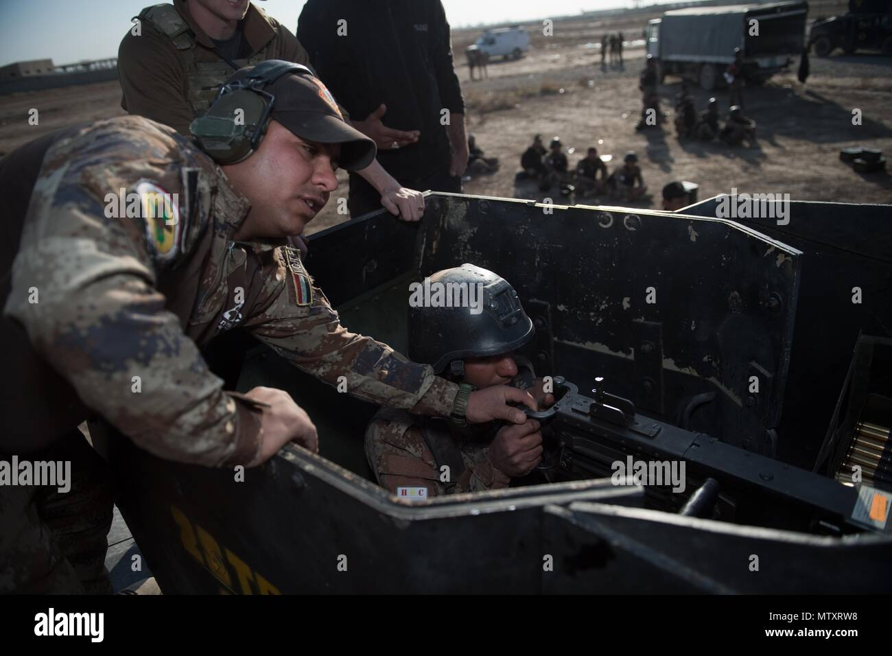 An Iraqi Counter-Terrorism Service instructor corrects a trainee operating the .50 caliber machine gun during live weapons training near Baghdad, Iraq, Jan. 31, 2017. ICTS is Iraq's elite counter-terrorism force and has proven to be an effective fighting force against ISIL. This training is part of the overall Combined Joint Task Force – Operation Inherent Resolve building partner capacity mission to increase the capacity of partnered forces fighting ISIL. CJTF-OIR is the global Coalition to defeat ISIL in Iraq and Syria. (U.S. Army photo by Staff Sgt. Alex Manne) - Stock Image