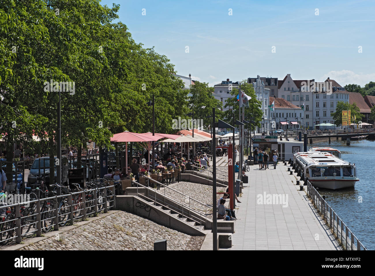 cafes with tourists on the bank of the trave river in the old town of lubeck, germany - Stock Image