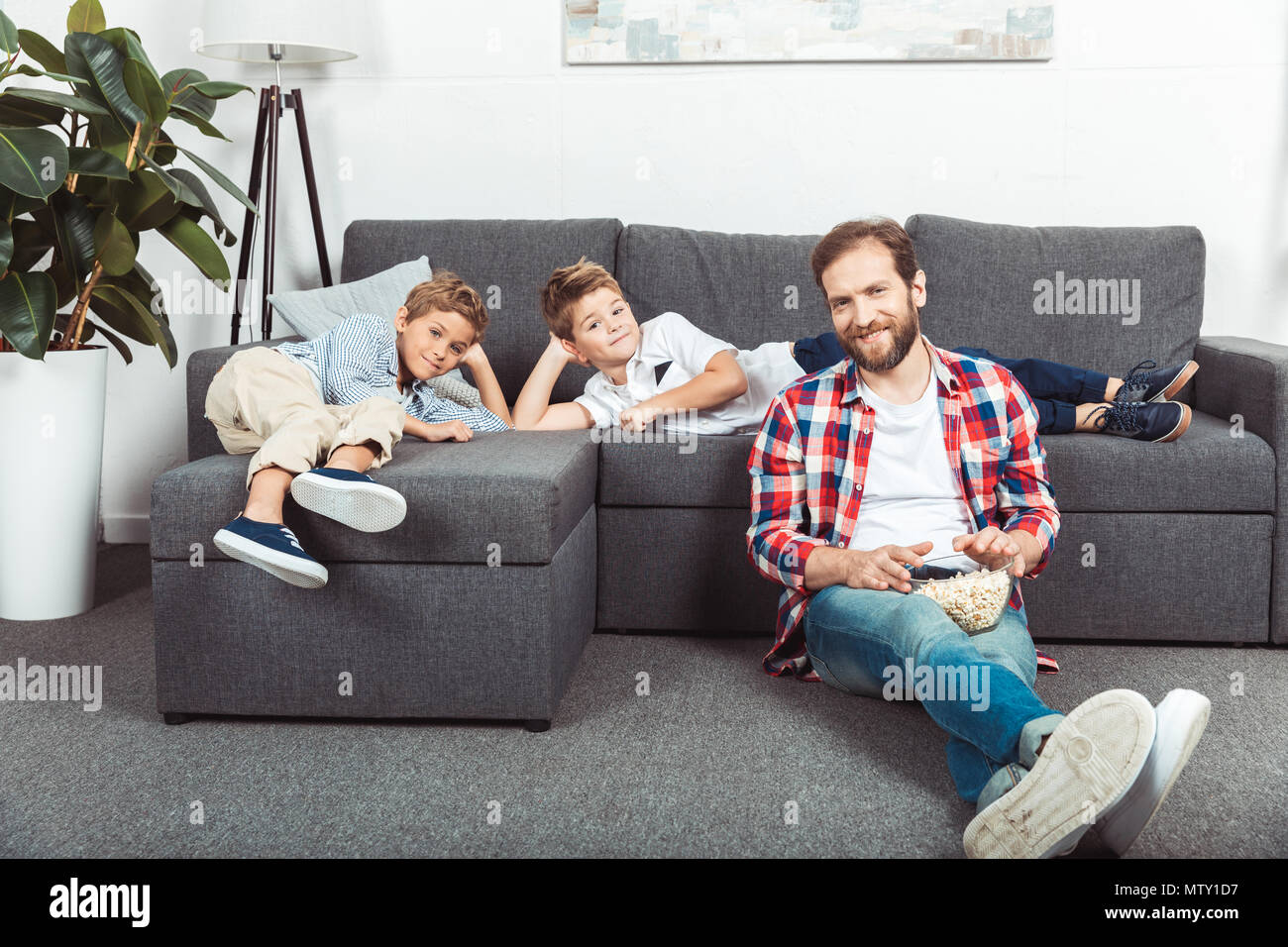 cute little brothers lying on sofa while smiling father eating popcorn at home - Stock Image