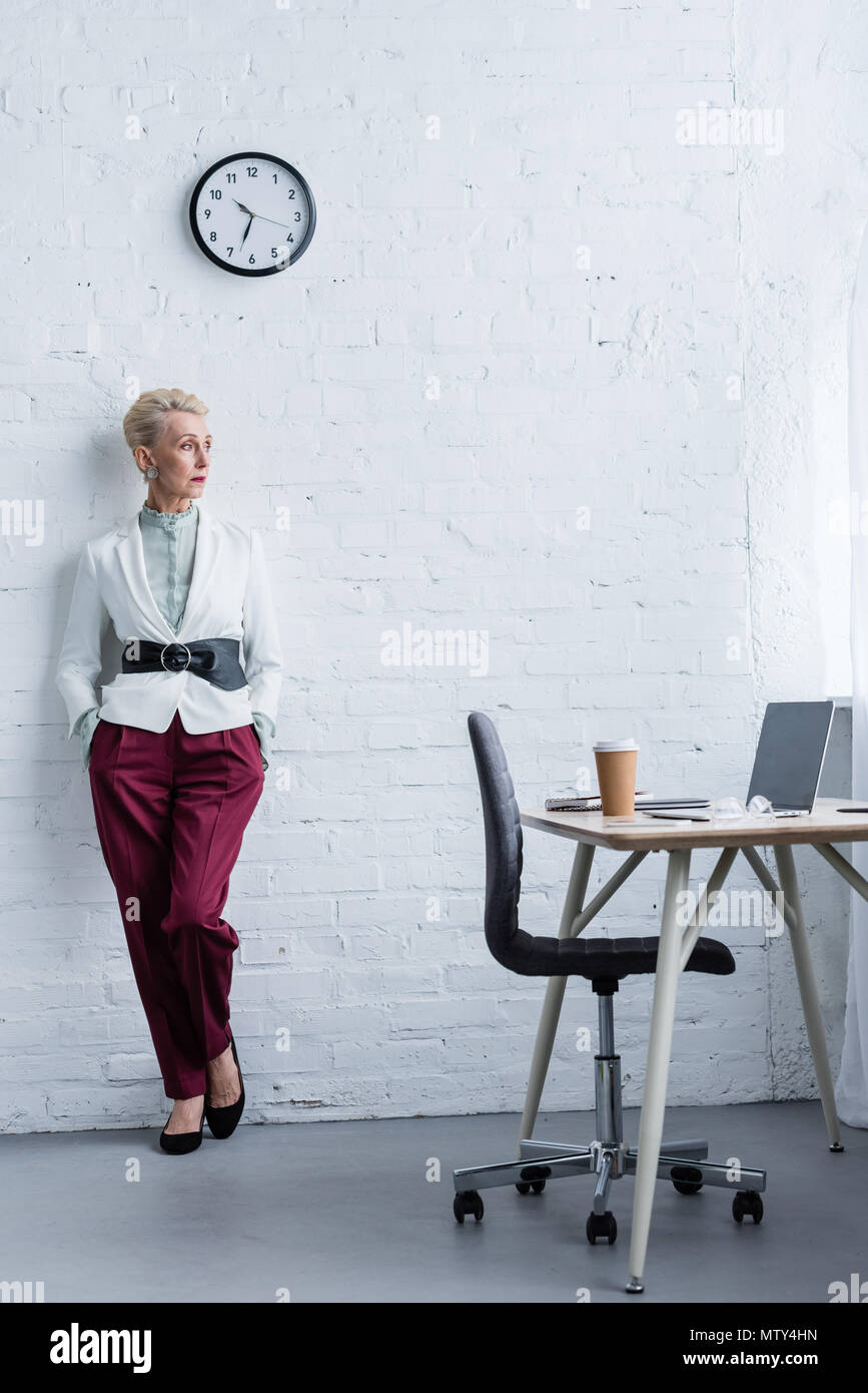 elegant senior businesswoman posing near workplace with laptop and coffee - Stock Image