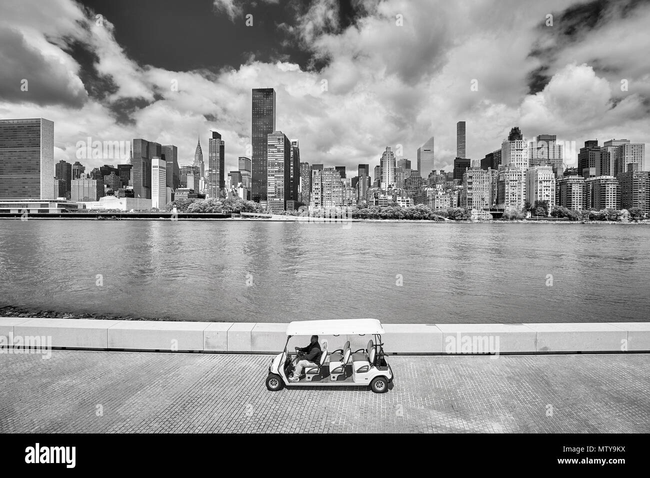 New York City, USA - May 26, 2017: Passenger golf cart on the Franklin D. Roosevelt Four Freedoms Park promenade, New York City skyline in background. - Stock Image