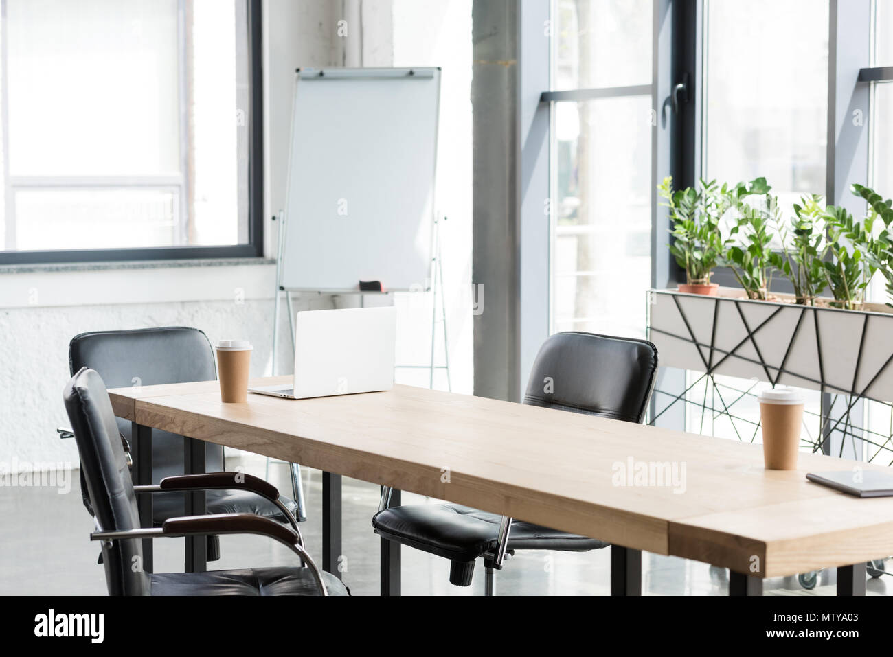 disposable coffee cups and laptop on wooden table in modern office - Stock Image