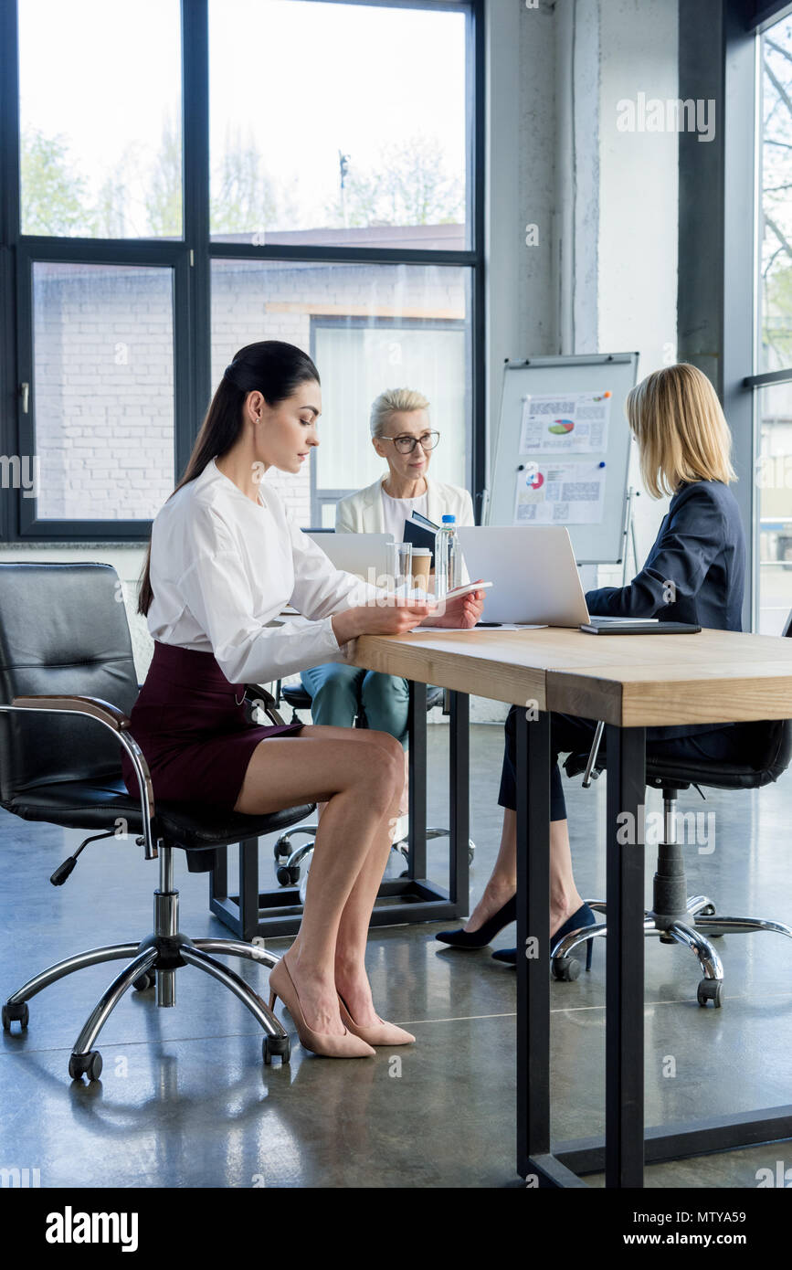 three professional businesswomen in formal wear working at table in office - Stock Image