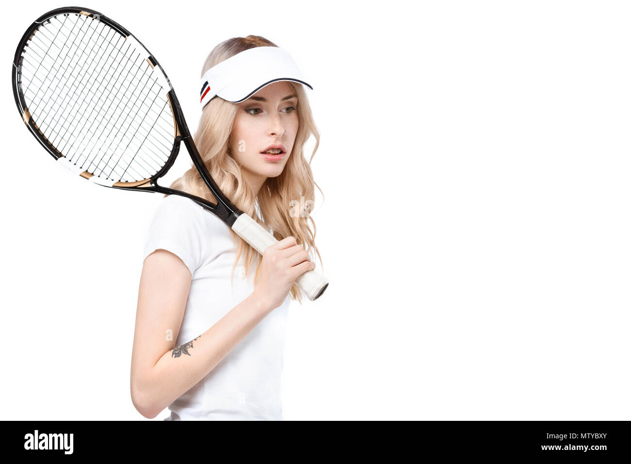 Half-length shot of a young woman with a tennis racket. - Stock Image