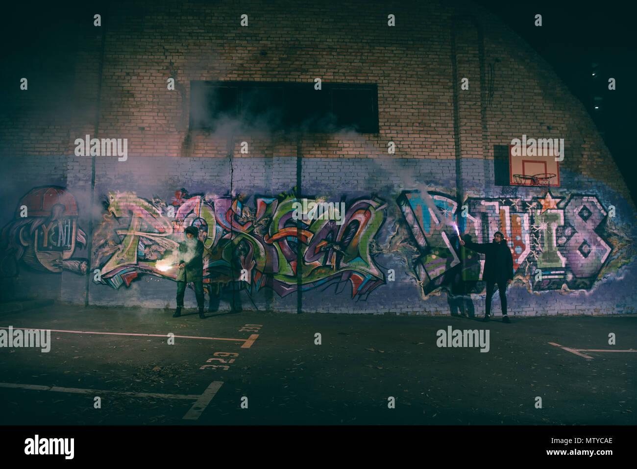 people holding smoke bombs and standing against wall with graffiti at night - Stock Image