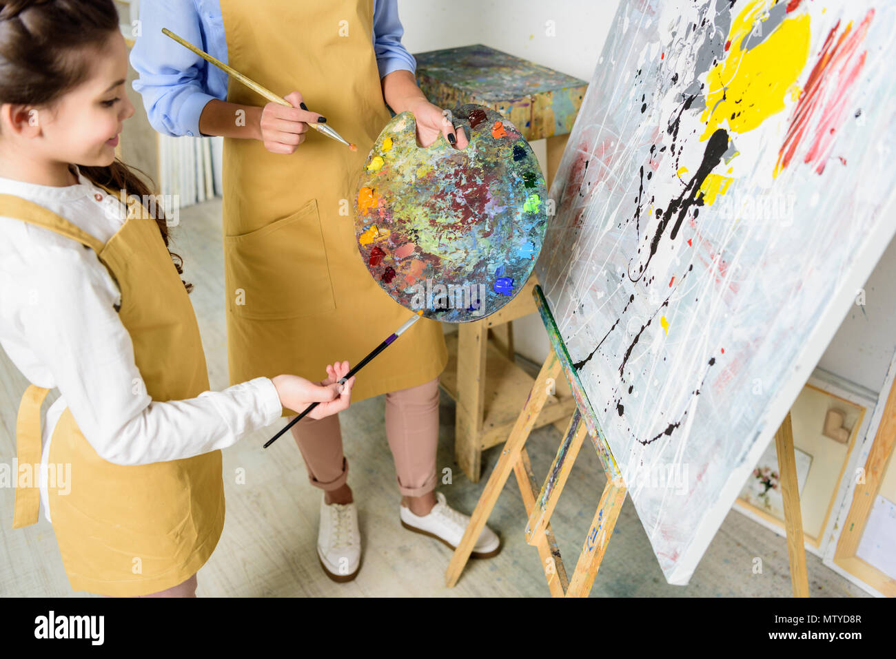 cropped image of teacher and pupil choosing paint on palette in workshop of art school - Stock Image