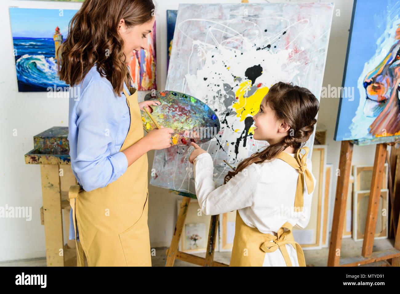 teacher and pupil choosing paint on palette in workshop of art school - Stock Image
