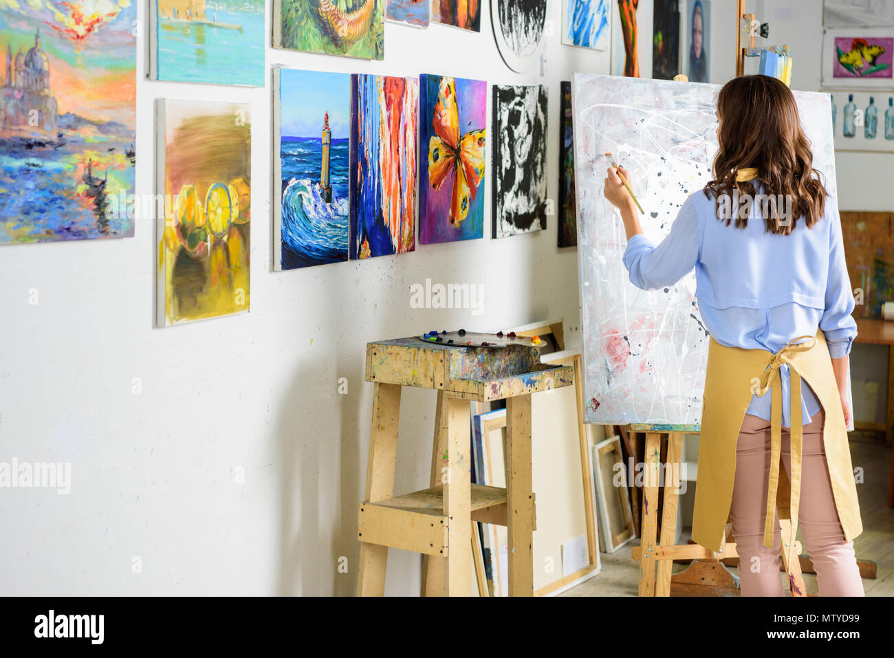 rear view of left-handed female artist painting on canvas in workshop - Stock Image