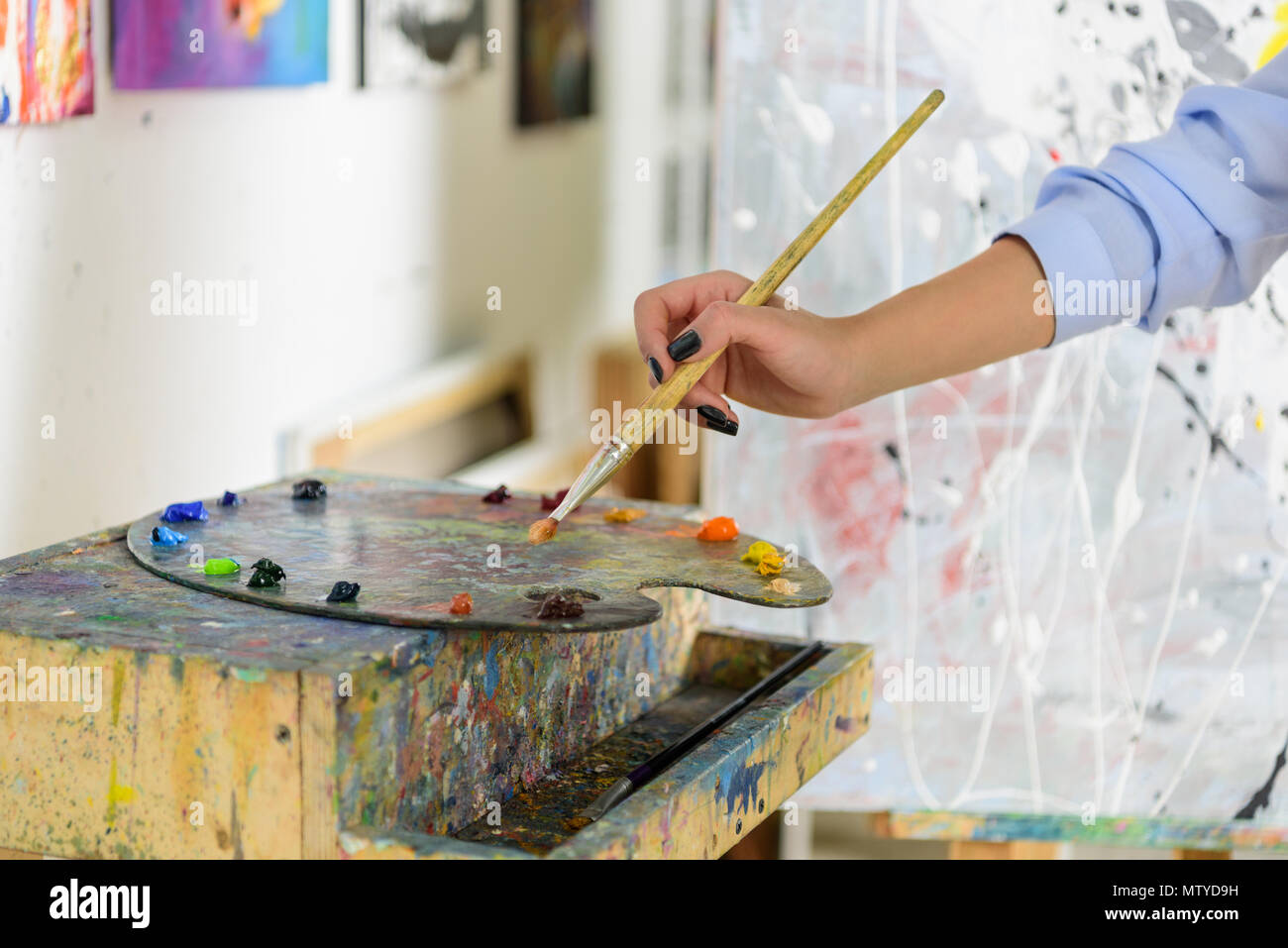 cropped image of artist taking paint from palette in workshop Stock Photo