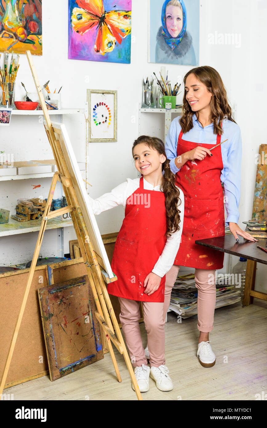 smiling teacher watching how pupil painting in workshop of art school - Stock Image