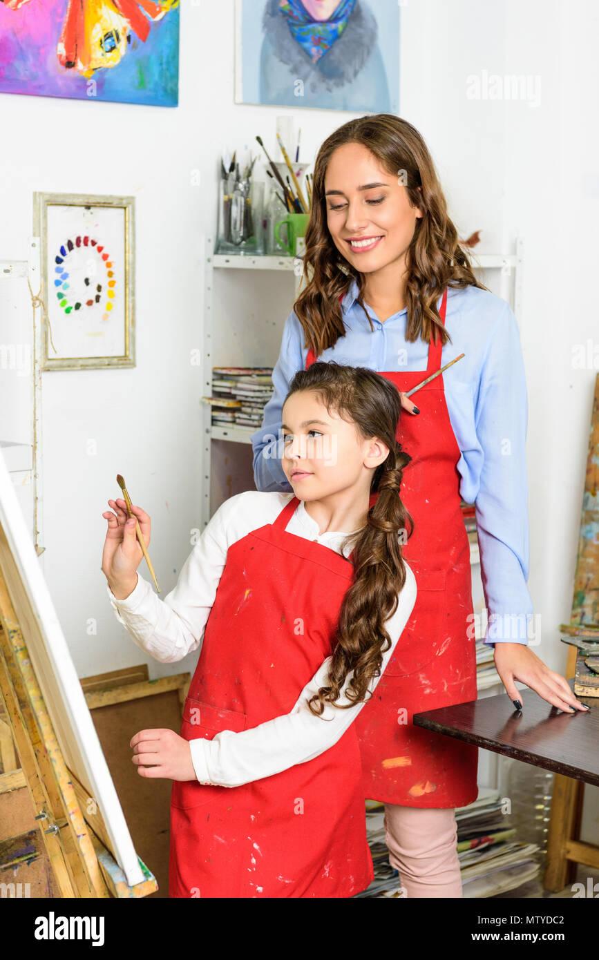 teacher watching how pupil painting in workshop of art school - Stock Image
