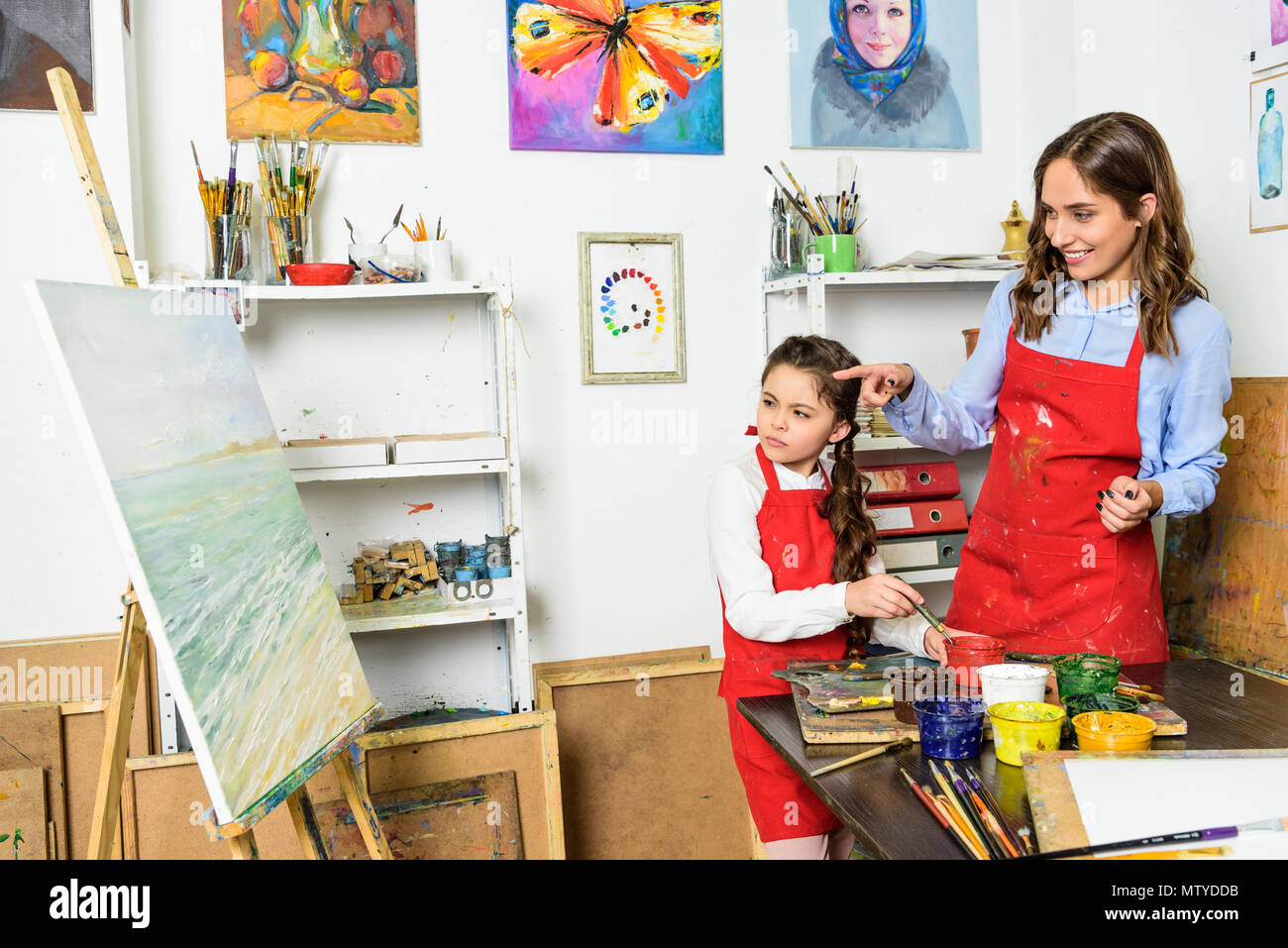 teacher pointing on pupil canvas in workshop of art school - Stock Image