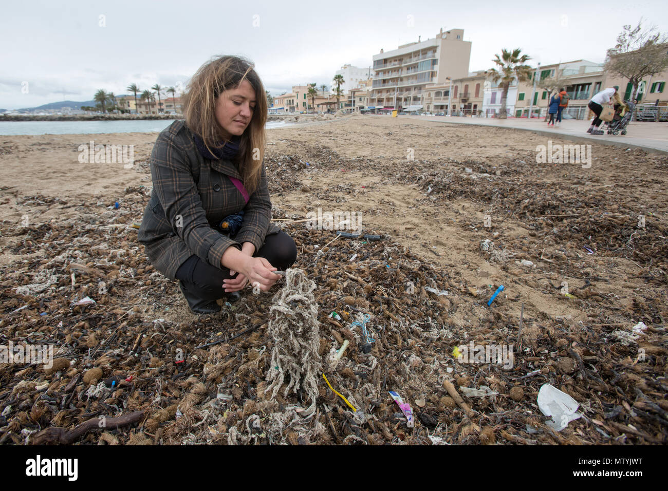 20 March 2018, Spain, Mallorca: Aina Barcelò from the environment organisation 'Ondine Baleares' examining rubbish on the beach in the Palma bay which has got mixed up with Neptune grass and sanitary products. Sewage works in Palma quickly become overburdened when it rains and raw sewage ends up flowing directly into the sea. The rubbish then lands on the beaches and mixes with the Neptune grass in the sand. Photo: Bodo Marks/dpa Stock Photo