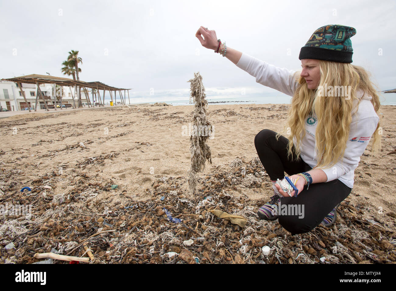 20 March 2018, Spain, Mallorca: Alice Mason from the environment organisation 'Ondine Baleares' examining rubbish on the beach in the Palma bay which has got mixed up with Neptune grass and sanitary products. Sewage works in Palma quickly become overburdened when it rains and raw sewage ends up flowing directly into the sea. The rubbish then lands on the beaches and mixes with the Neptune grass in the sand. Photo: Bodo Marks/dpa Stock Photo
