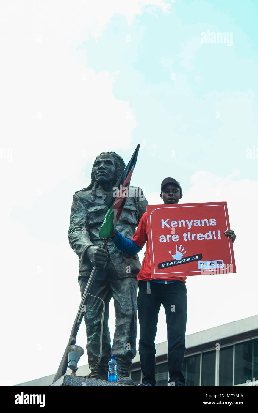 Nairobi, Kenya. 31st May, 2018. A protestor carry placard standing next to the statue of freedom fighter Dedan Kimathi as Kenyans protested in the streets. Protesters take the street to call the government to arrest people involved in massive corruption scandals. In a recent scandal involving National Youth Service (NYS), the Kenyan government lost Ksh9 billions in dubious tender deals. Credit: Allan Muturi/SOPA Images/ZUMA Wire/Alamy Live News - Stock Image