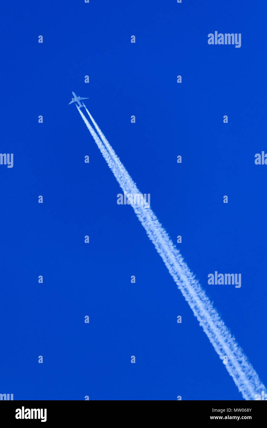 A commercial jet flies against a deep blue sky with a long contrail behind it. - Stock Image