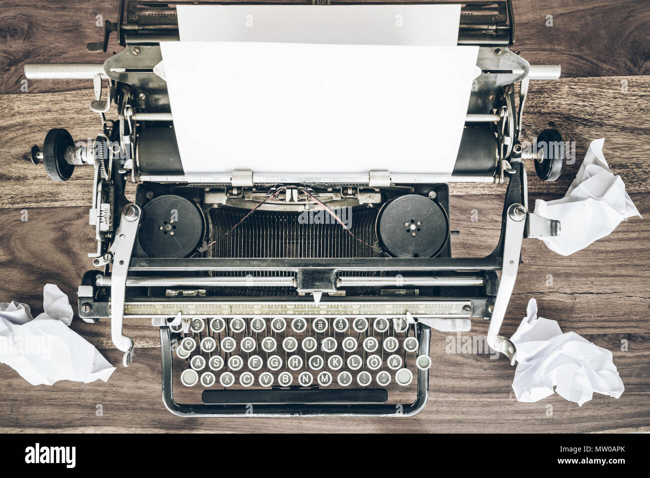 top view of old manual typewriter and crumpled sheets of paper on rustic wooden desk - Stock Image