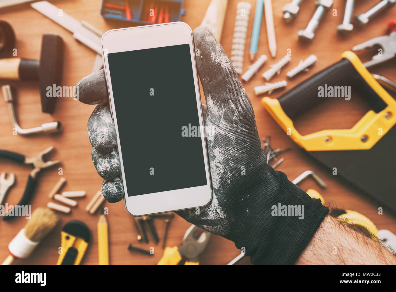 Smart phone app for handyman, repairman holding mobile phone