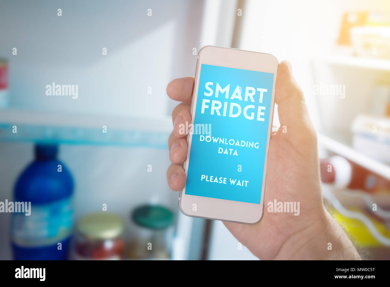 Internet of things, smartphone connecting with refrigerator to generate smart shopping list. Home kitchen appliance connecting with mobile phone and e Stock Photo