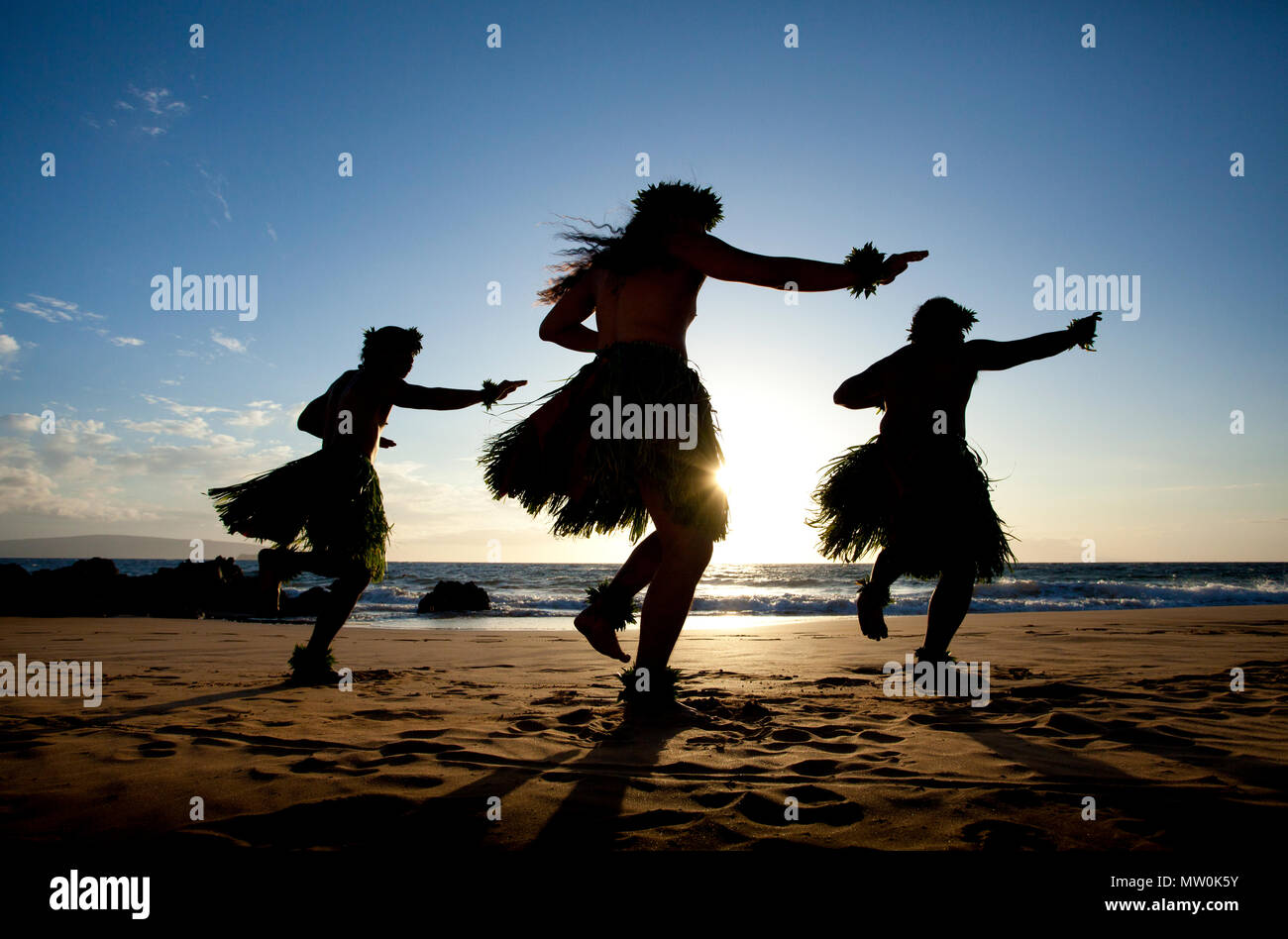 Three male hula dancers at sunset at Wailea, Maui, Hawaii. - Stock Image