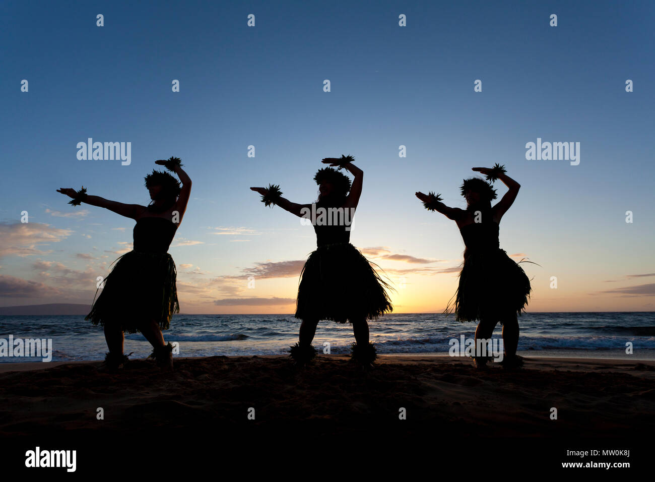 Three hula dancers at sunset at Wailea, Maui, Hawaii. - Stock Image