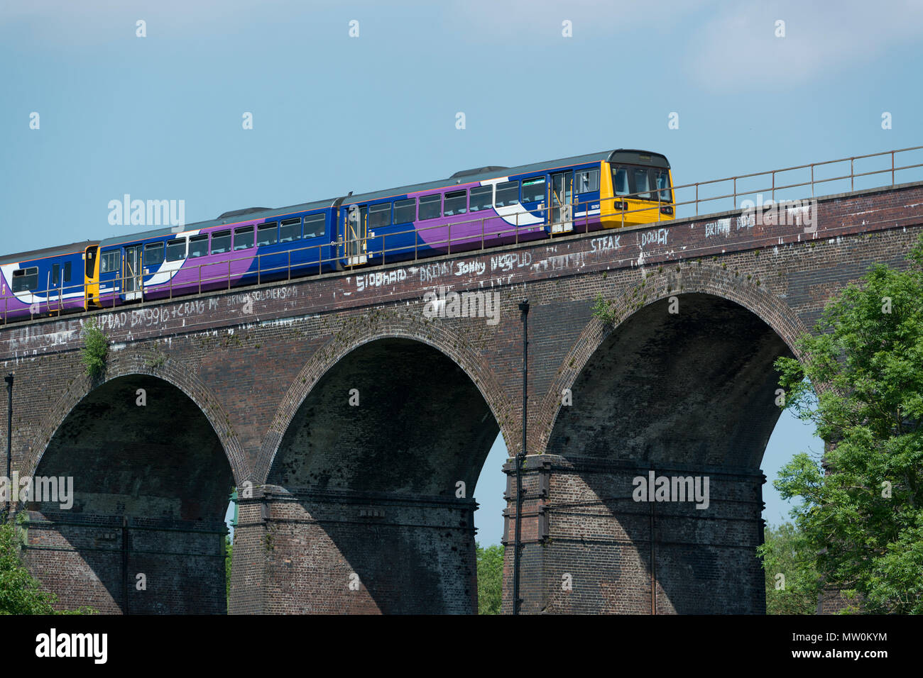 A Northern Rail pacer train passes over a railway viaduct which crosses Reddish Vale Country Park in Stockport, Greater Manchester, UK - Stock Image
