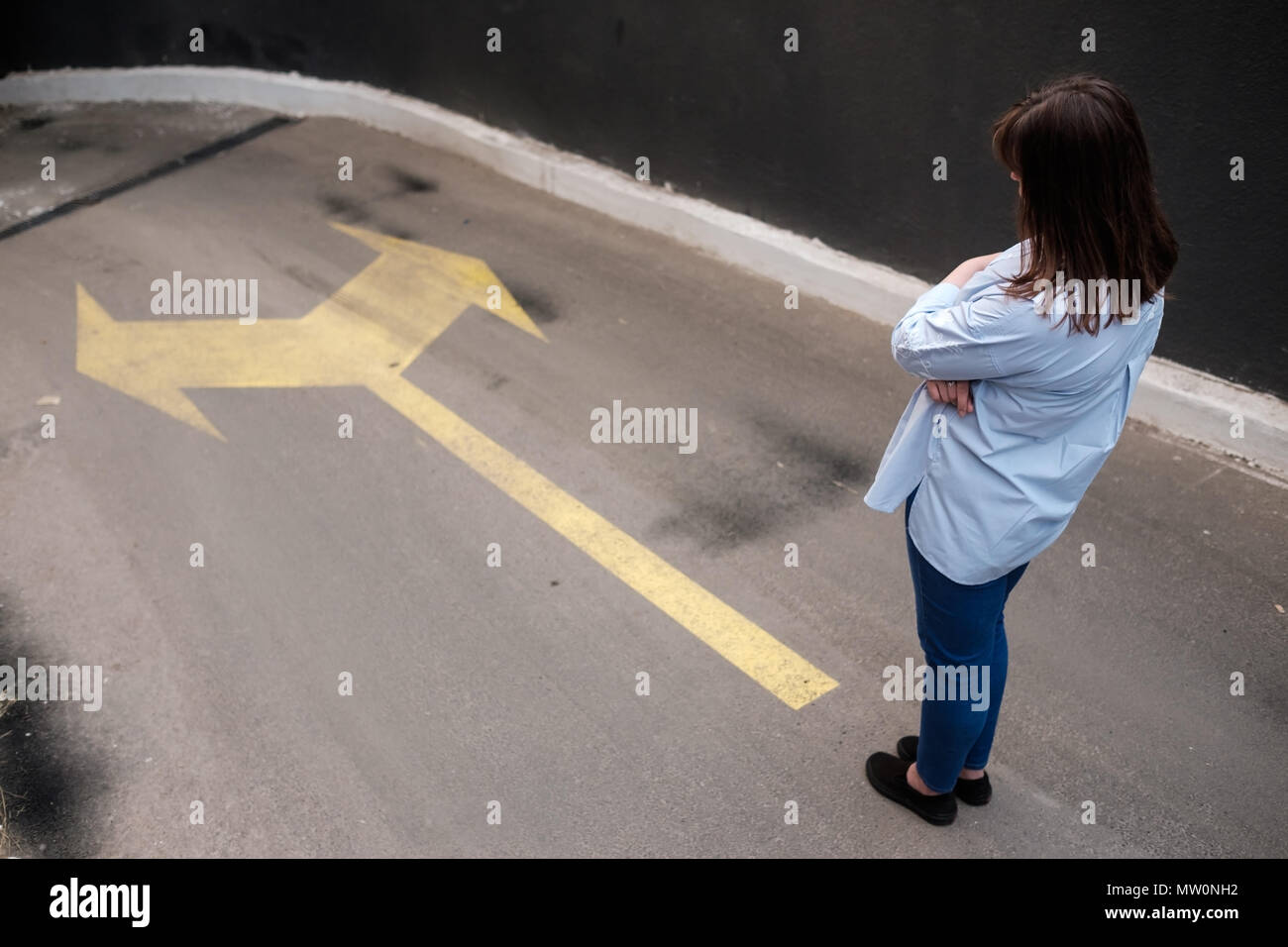 Firl standing near two arrows printed on grunge road, making decision - Stock Image