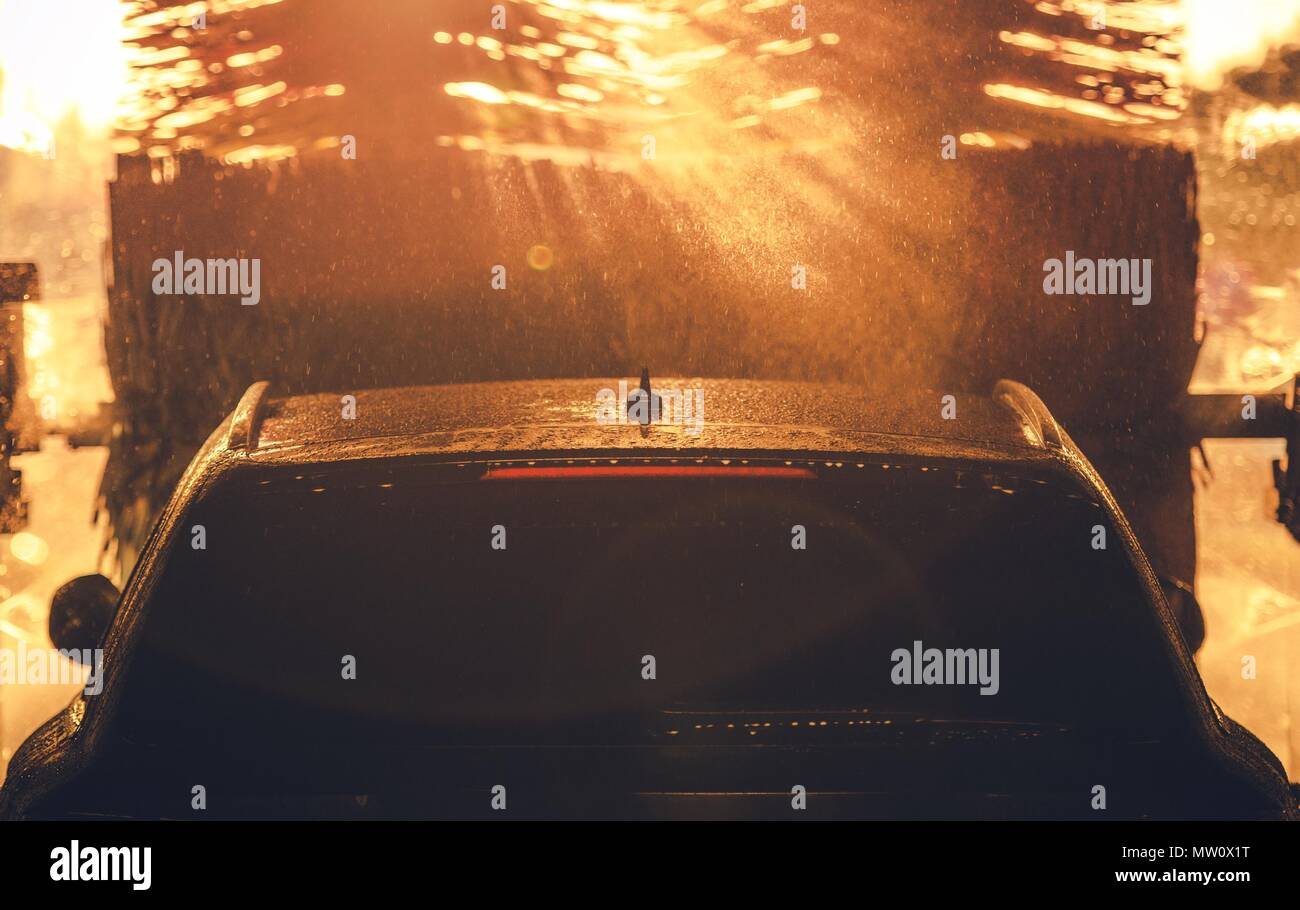 Car Washing in the Sun. Sun Rays Between Car Wash Brushes. Transportation Industry Theme. - Stock Image