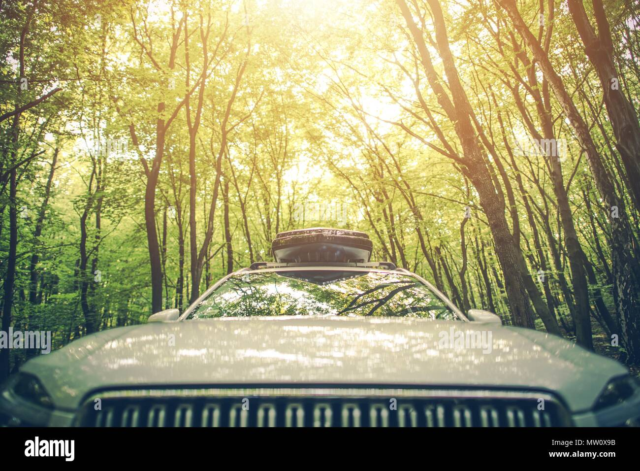 Vacation Road Trip with Cargo Roof Container on the Vehicle. Driving Through The Summer Forest. - Stock Image