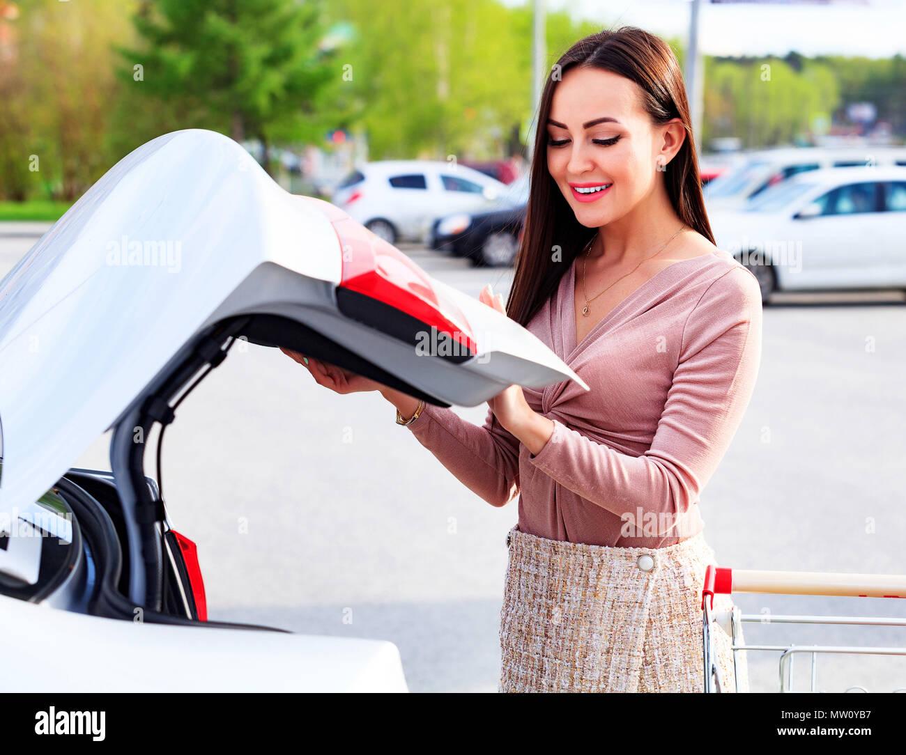 Young pretty woman is opening the trunk of her car - Stock Image